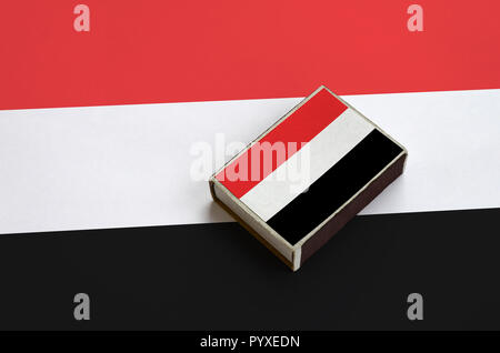 Yemen flag  is pictured on a matchbox that lies on a large flag. - Stock Photo