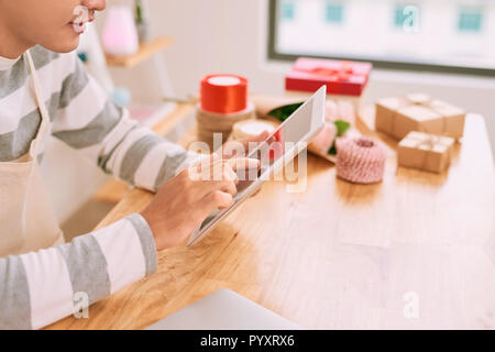 Joyful pleasant male seller working with digital tablet in a gift shop. - Stock Photo