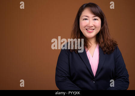 Mature beautiful Asian businesswoman against brown background - Stock Photo
