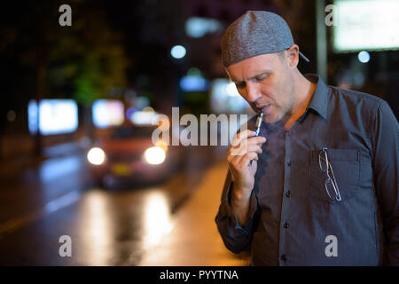 Mature man smoking electronic cigarette in the streets at night - Stock Photo