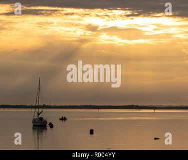 a single sailing boat on calm seas at sunset with light rays coming through the clouds - Stock Photo