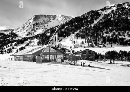 Slopes of Winter Resort El Tarter and Pyrenees Mountains in Andorra la Vella. Restaurant and cafe building, unidentified people skiing. Black and whit - Stock Photo