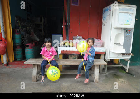 Kiulu Sabah Malaysia - Oct 18, 2017 : Two kids playing with beloon infront of sundry shop in Kiulu Sabah. Kiulu is one of main tourist destination in  - Stock Photo