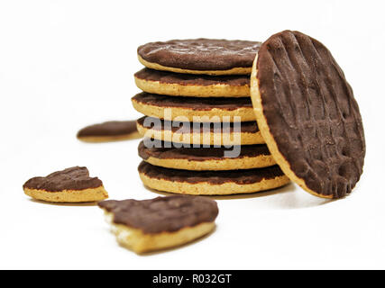 Stack of whole wheat diet biscuits. Dark chocolate covered cookies on white background - Stock Photo