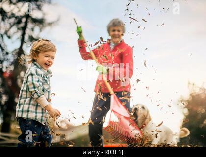 Grandmother raking leaves with grandson. - Stock Photo