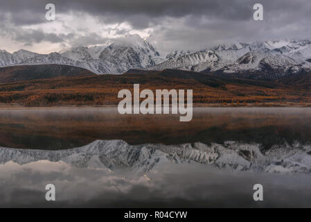 Colorful autumn view with mountains covered with snow and golden forest, clouds, fog and their reflections in the lake before dawn - Stock Photo