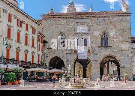 Old Town Palace (Palazzo della Ragione) on Piazza Vecchia with fountain and crowd in Citta Alta, Bergamo, Lombardy, Italy, Europe - Stock Photo