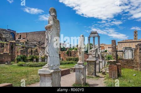 Roman statues at the site of the House of Vestals in the Roman Forum with the three remaining Corinthian columns of the Temple of Castor and Pollux in - Stock Photo