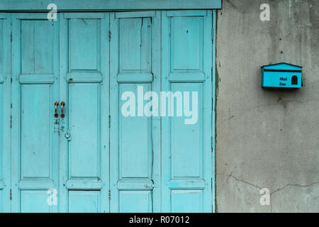 Closed green or blue wooden door and empty mail box on cracked concrete wall of house. Old home with cracked cement wall. Vintage front door abstract  - Stock Photo