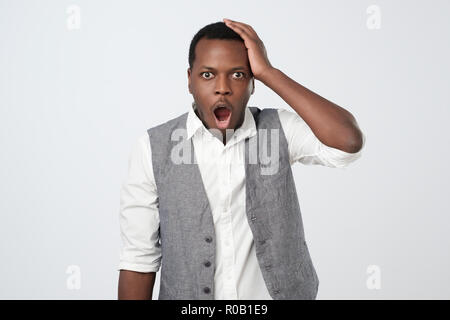 Puzzled or suprised african man dressed in white shirt and vest looking in shock and frustration - Stock Photo