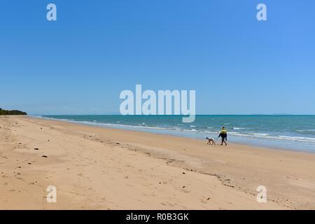 Man walking dog along deserted beach, Balgal beach, QLD, Australia - Stock Photo
