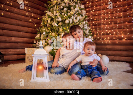 Three happy children - teenager boy, toddler girl and their newborn baby brother - playing together under a beautiful Christmas tree. Boys are sitting - Stock Photo