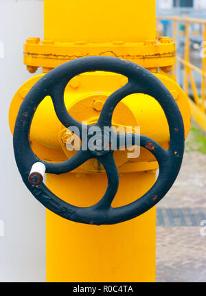 Large black manual handwheel in a control valve on a bright yellow pipe - Stock Photo