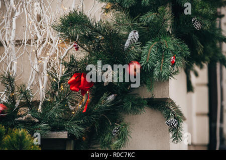 Stylish christmas decorations, green christmas wreath with red bows and ornaments, pine cones, stars, white branches in european city street. Festive  - Stock Photo