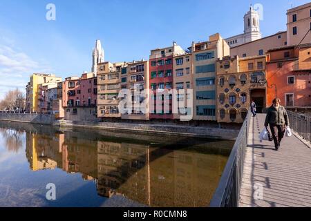 Woman along a pedestrian bridge in Rio Onyar Ciudad Vieja , Old Town with coloured houses, Girona, Catalonia, Spain - Stock Photo