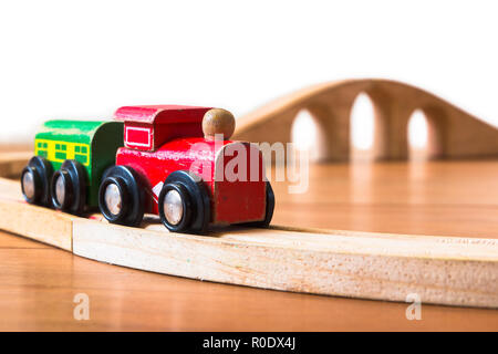 Wooden toy train on railroad with bridge in backdrop - Stock Photo