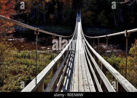 A horizontal image of a suspension bridge crossing the Hammond River at Upham in rural Saint John county New Brunswick, Canada. - Stock Photo