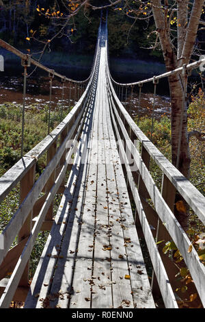 A vertical image of a suspension bridge crossing the Hammond River at Upham in rural Saint John county New Brunswick, Canada. - Stock Photo