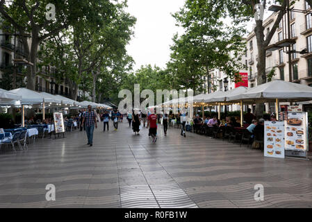 People walking along La Rambla passing several restaurants, Barcelona, Spain - Stock Photo