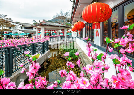 Hong Kong, China - January 26, 2016: Tea House exterior in Ngong Ping 360 village on Lantau Island decorated with blooming sakura branches and red fes - Stock Photo