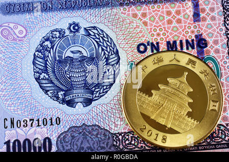A macro image of an Uzbek ten thousand som bank note with a gold Chinese one ounce panda coin - Stock Photo