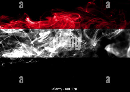 National flag of Yemen made from colored smoke isolated on black background. Abstract silky wave background - Stock Photo
