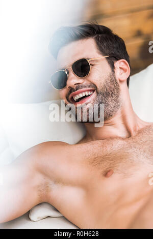 smiling handsome shirtless man in sunglasses lying on sun lounger - Stock Photo