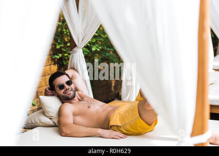 smiling handsome shirtless man in sunglasses lying on sun lounger and looking at camera - Stock Photo