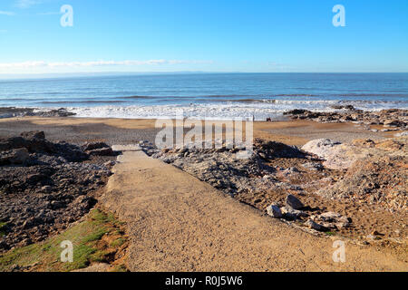 A small bay along the coastline with a few well wrapped up people looking out to sea on a cool day complete with family pet on a deserted beach. - Stock Photo