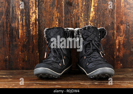 women's comfortable winter boots on a wooden background. place for text - Stock Photo