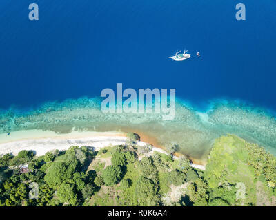 A Pinisi schooner sails near an island in the Banda Sea, Indonesia. - Stock Photo