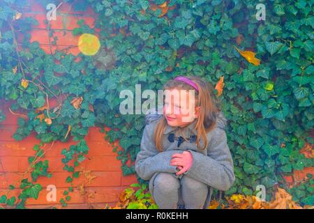 Little girl wearing retro coat and crouching in front of brick wall in autumn. Ivy wall in autumn. Autumn concept. Lens flare - Stock Photo