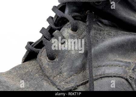 Old black dirty shoes. Leather military footwear on a white table. Light background. - Stock Photo