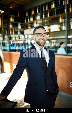Young confident entrepreneur in suit standing on entrance of cafe and meeting guests or new clients - Stock Photo