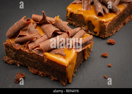 Chocolate Brownies with salted caramel sauce and chocolate flakes - Stock Photo