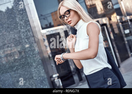Business woman blond in glasses hurrying to a meeting - Stock Photo