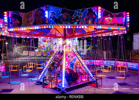 A deserted neon-lit carousel in a fun fair in Machynlleth, Wales, UK - Stock Photo