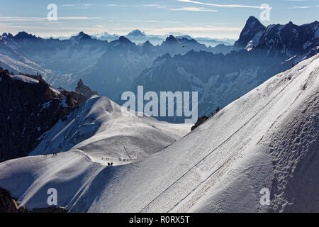 Chamonix, south-east France, Auvergne-Rhône-Alpes. Climbers heading for Mont Blanc. Descending from Aiguille du Midi cable car station towards sunny s - Stock Photo