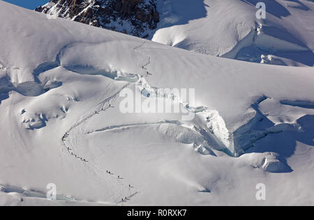 Pointe Lachenal, Chamonix, south-east France, Auvergne-Rhône-Alpes. Climbers heading for Mont Blanc - scaling Pointe Lachenal's glacier crevasse with  - Stock Photo