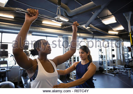 Personal trainer helping woman using exercise equipment in gym - Stock Photo