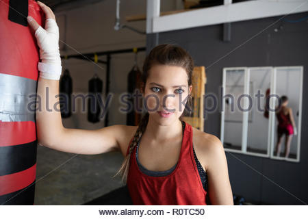 Portrait confident, tough female boxer at punching bag in gym - Stock Photo