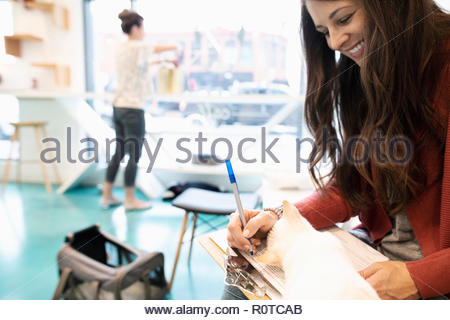Happy woman adopting kitten, filling out application in cat cafe - Stock Photo