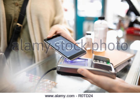 Close up female shopper making smart phone payment in shop - Stock Photo