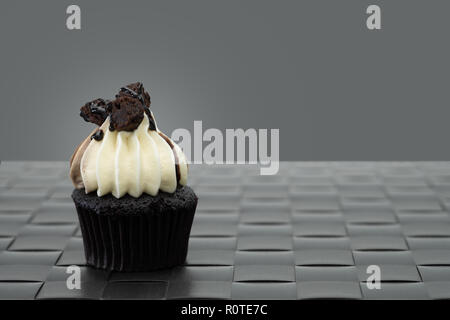 Tasty chocolate mini cupcakes on a vintage background, sweet dessert. - Stock Photo