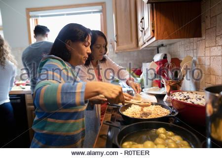 Latinx senior women cooking in kitchen - Stock Photo