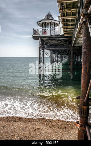 solitary hooded figure on brighton pebble beach - Stock Photo