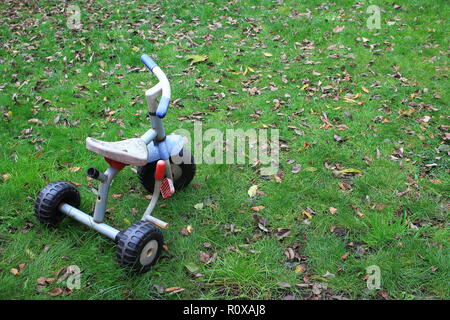 Old child tricycle three wheels bike in the garden - Stock Photo