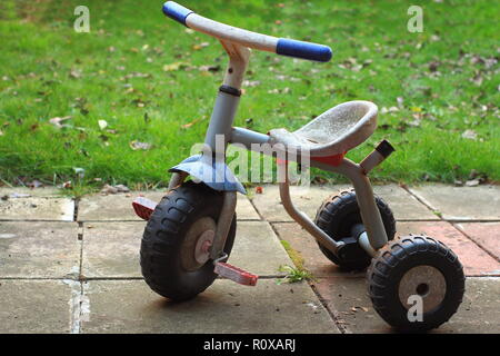 Vintage baby tricycle three wheels bike in the garden - Stock Photo