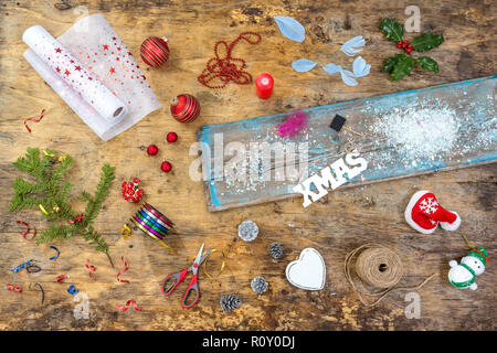 Accessories, Preparing for Christmas. Holiday decoration toys, garlands, lights, wreath over old vintage wooden table ,top view - Stock Photo