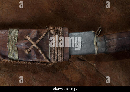 Part of hidden in the stick Real japanese samurai sword on brown leather - Stock Photo